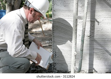 A building inspector checking out the foundation of a new building.