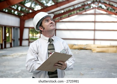 A building inspector examining the the steel girders in a building under construction.  Horizontal view.