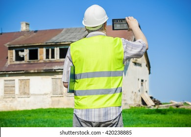 Building inspector filming on tablet PC near old abandoned, damaged house on grass field