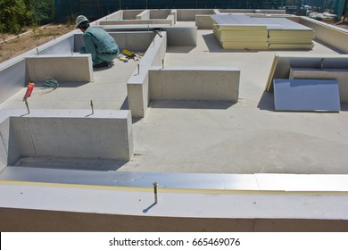 A building inspector wearing a hard hat carefully checks the concrete foundation of a house and the insulation work being done with special energy efficient, sliver colored heat reflective panels.