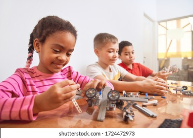 Building kit with colorful pieces for group of three multiracial kids creating toys, having positive emotions. Close up of smiling african girl working on project. Concept of science engineering.