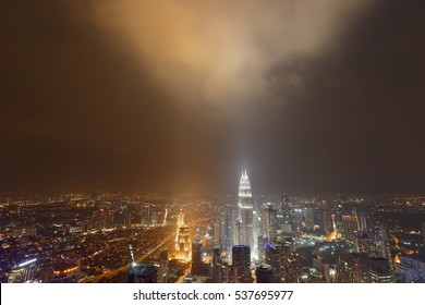 Building lights reflecting off low clouds at night time. Kuala Lumpur, Malaysia.