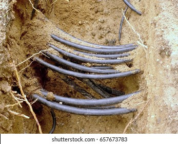 Building of lines of metallic and fiber optic cables, construction of communication optical network connection. Laying underground tow cable. Excavation of trench by hand o