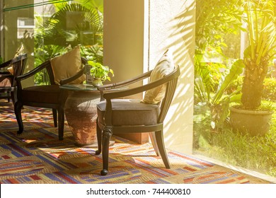 The building lobby or living room with furniture such as chairs table on the carpet and other decorative stuff of pillow and mug of green plant with the garden background and flare.