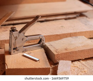 building metal stapler with staples on a wooden floor.  construction photos
