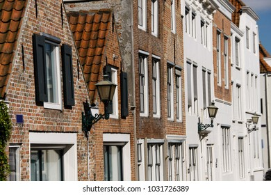 Building in Middelburg, Netherlands, details of old facade, wall with windows and wooden shutters.