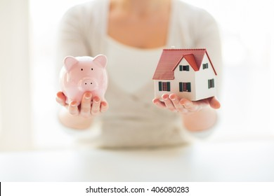 building, mortgage, investment, real estate and property concept - close up of woman holding home or house model and piggy bank