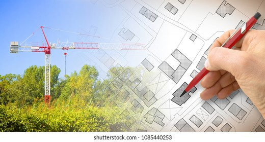 Building a new city - concept image with and drawing an imaginary cadastral map of territory with buildings, fields and roads and a tower crane in a construction site