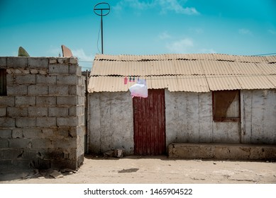 Building new home at African slum. White pink clean little baby girl dress hanging on clothesline from old rusty house to new concrete wall, Espargos town outskirts, Sal, Cape Verde Islands, Africa.