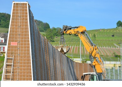 Building of a Noise Barrier in Steel Cage Construction surrounding a Development Area, manteled with Geotextile, filled with excavated soil