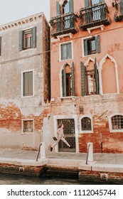 Building with old balconies. Classical European architecture. Vintage facade with balconies. A young woman enjoys the view. Colorful renaissance in Venice, Italy. Cut street background for web site.