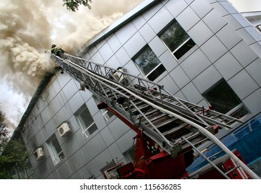 Building on fire. firefighter puts out a fire while on a ladder