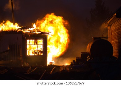 The building is on fire. The house is burned in the fire in the evening. Flames destroy the building at night.