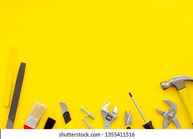 building, painting and repair tools for house constructor work place set yellow background top view space for text