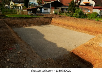 Building pit single-family house. Excavation pit with gravel pad for single-family dwelling. Basis for the cellar. Different layers of earth. Topsoil and loam.