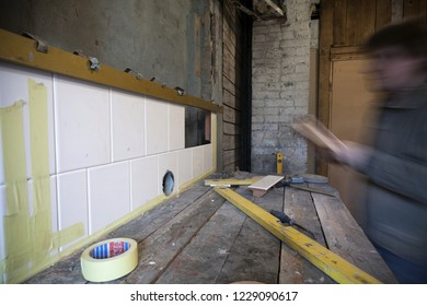Building process of traditional cooking stove of glazed white tiles. Stove builder's motion blurred. Photographed in Estonia, Europe.