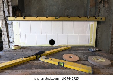 Building process of traditional woodstove of glazed white tiles. Spirit level fixed to tiles by metal clips.  Photographed in Estonia, Europe.