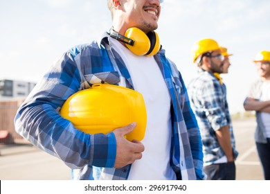 building, protective gear and people concept - close up of builder holding yellow hardhat or helmet at construction site