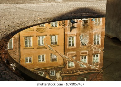 Building reflection/Shallow water surface on a street fountain reflecting a building in the old town main square of Warsaw.