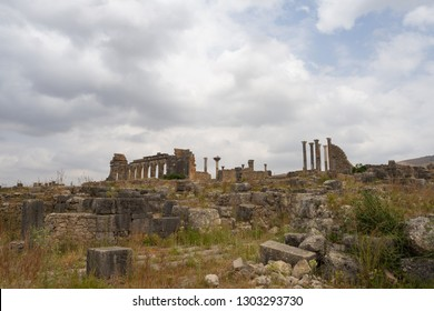 Building ruins on the amazing ancient site of Volubilis, with the basilica an Capitol on the background. Volubilis, Morocco.