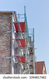 Building with a scaffolding with red planks in front of a blue sky