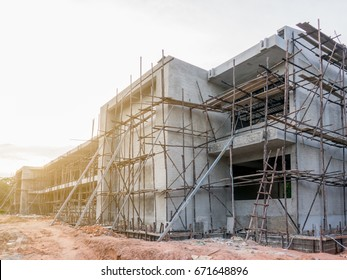 Building school under construction. The Building construction  has wooden structure for plastering and paint. Structure is color of concrete mortar and background is sky and cloud sunshine.