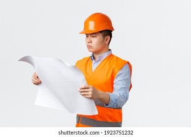 Building sector and industrial workers concept. Serious-looking asian construction manager, architect studying blueprints, looking at layout with serious face, standing white background in helmet