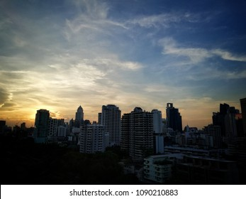 The building in the shadow at the evening time be fore end the day. The tall building in the Bangkok city, capital city of Thailand. In the Bangkok city have a lot of business a lot of worker.