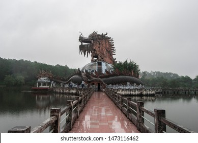 Building shaped like a dragon on an island in the middle of a lake on a rainy day. Sinister, creepy ambiance. Shot in Hue's abandoned water park, Vietnam.