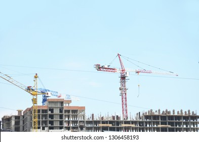 Building site background. Construction site with crane and building. Construction crane near the building. near old houses