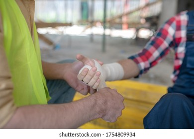 Building site. Close-up of building worker hands applying bandage on his coworker forearm