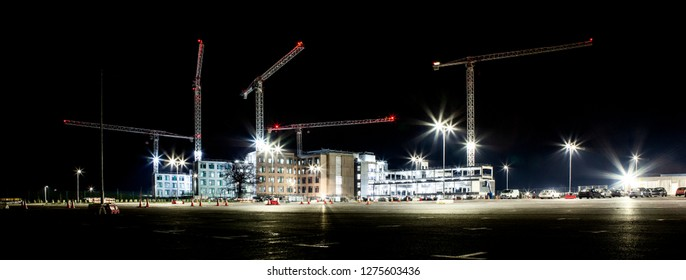 Building site with cranes by night