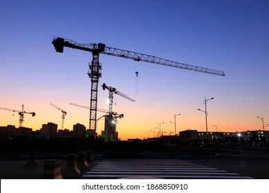 Der Bauplatz ist abends, die Turmkrane bauen Wohngebäude
