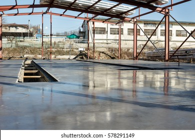 Building site - fresh polished concrete slab with reflections and metal construction