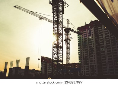 Building site with high-rise block under construction in an urban environment dominated by a large industrial crane silhouetted against sunset sky