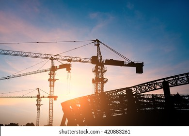 Building site with high-rise block under construction in an urban environment dominated by a large industrial crane silhouetted against a cloudy blue sky