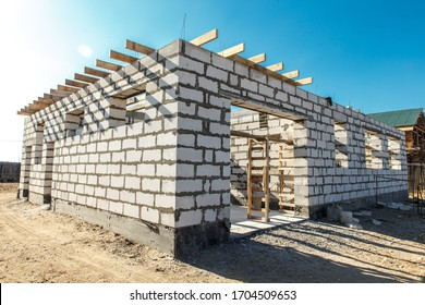 Building site of a house under construction. corner unfinished house walls made from white aerated autoclaved concrete blocks.