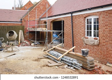 Building site in UK with brick house extension under construction