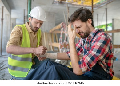 Building site. Building worker applying bandage on his coworker forearm, frowning from pain and closing his face with hand