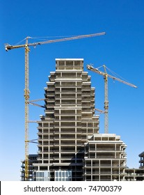 Building of a skyscraper with two tower cranes
