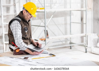 Building supervisor in hardhat perched on a workbench with blueprints working on his laptop in a building under construction