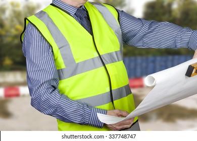Building surveyor in hi vis checking site plans holding spirit level