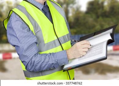 Building surveyor in hi vis checking data in site folder
