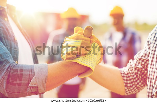 building, teamwork, partnership, gesture and people concept - close up of builders hands in gloves greeting each other with handshake on construction site