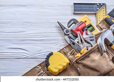 Building tooling in tool belt on wooden board construction concept.