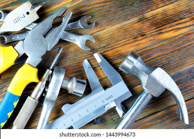 Building tools on wooden background, holiday, fathers day. Popular locksmith tools for creativity and business - the hammer of the carpenter, mechanic pliers, screwdrivers, wrenches, calipers.