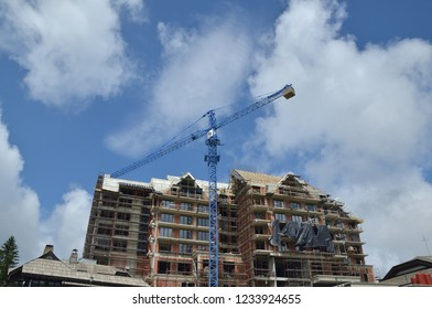 Building under construction with a crane against blue sky with clouds