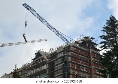 Building under construction with cranes against cloudy sky