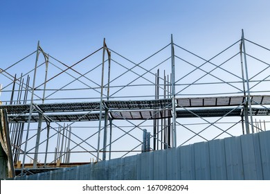 building is under construction with metal scaffolding and cloudy sky