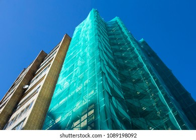 Building under construction with scaffolds and safety net against blue sky